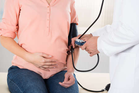 midsection: Midsection of male doctor checking pregnant womans blood pressure in hospital