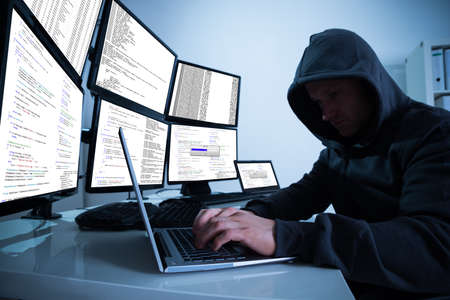 multiple: Hacking laptop against multiple monitors at desk Stock Photo
