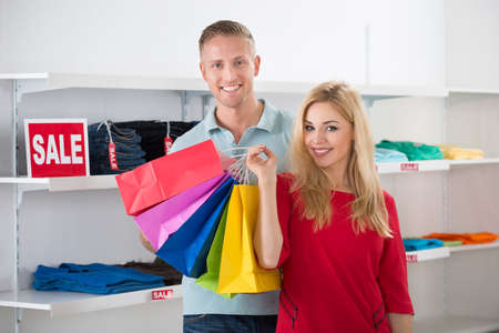 fabric bag: Smiling man looking at woman carrying shopping bags in store