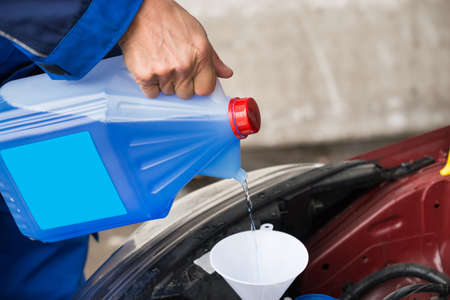 antifreeze: Cropped image of mature serviceman pouring windshield washer fluid into car at service station