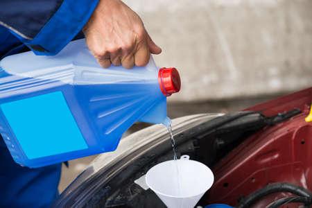 envases plasticos: Imagen recortada de militar madura verter líquido limpiador de parabrisas en el coche en la estación de servicio