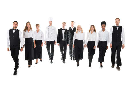 hospitality staff: Full length portrait of confident restaurant staff walking in row against white background
