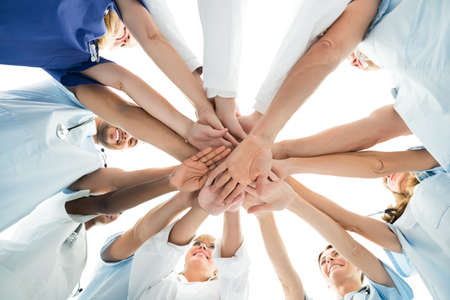 staff team: Directly below shot of multiethnic medical team stacking hands over white background