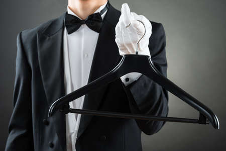 hospitality staff: Midsection of male housekeeper holding hanger against gray background Stock Photo