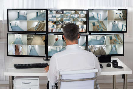 footage: Rear view of security system operator looking at CCTV footage at desk in office Stock Photo
