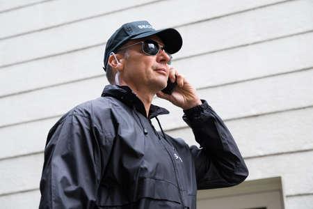 earpiece: Confident mature security guard listening to earpiece against building