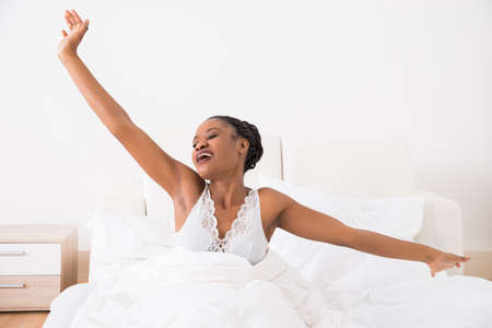 gente durmiendo: Portrait Of A Young African Woman Stretching Her Arms On Bed Foto de archivo