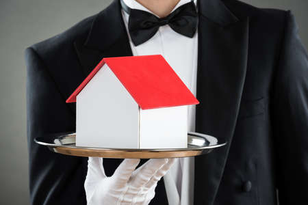 hospitality staff: Midsection of young waiter holding house model in tray against gray background
