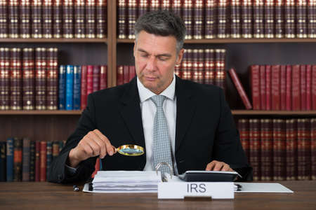 auditor: Mature male tax auditor examining documents with magnifying glass at table in office