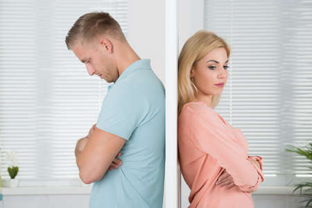 Side view of unhappy young couple standing back to back at home Stock Photo