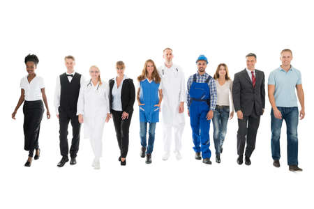 group of workers: Full length portrait of confident people with various occupations walking in row against white background
