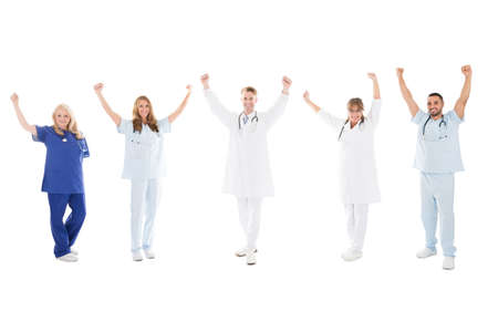 isolated man: Full length portrait of happy medical team standing with arms raised against white background
