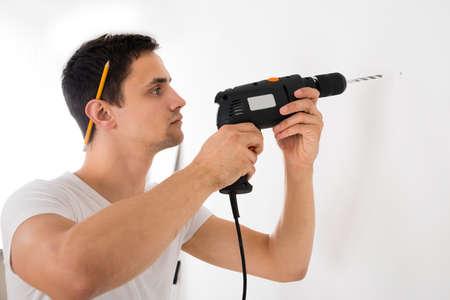 taladro: Hombre joven que usa el taladro de potencia en la pared blanca en casa Foto de archivo