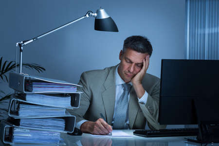 Tired businessman with hand on face writing on document while working late in office Stock fotó