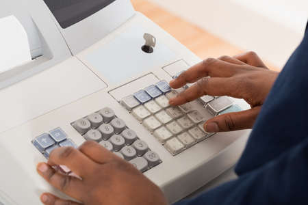 sales person: Close-up Of A Sales Person Entering Amount On Cash Register