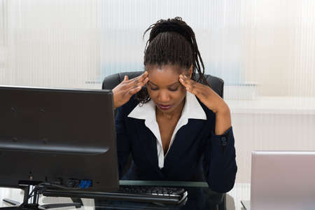 Stressed African Business Woman Sitting At Office Desk