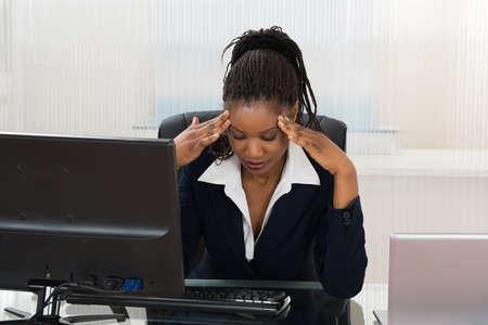 Tensionado africana de negocios sentado en el escritorio de oficina