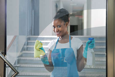 office uniform: Portrait Of Smiling African Woman Cleaning Glass With Rag