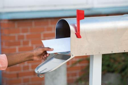 cartero: Primer plano de la mano de la persona que pone letras en Buzón