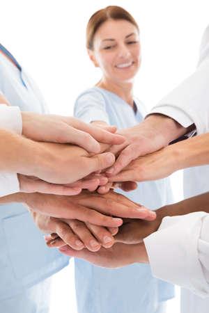 manos juntas: Imagen recortada de equipo médico de apilamiento manos contra el fondo blanco