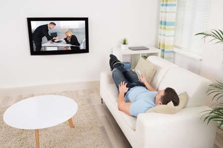 man scolding: Relaxed mid adult man lying on sofa while watching movie in living room Stock Photo