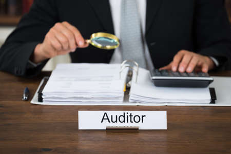 auditor: Midsection of male auditor scrutinizing financial documents at table in office