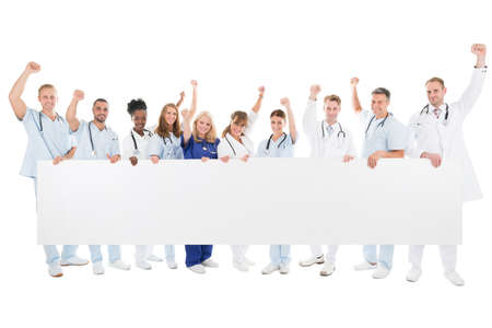 placard: Full length portrait of medical team with arms raised holding blank billboard against white background Stock Photo