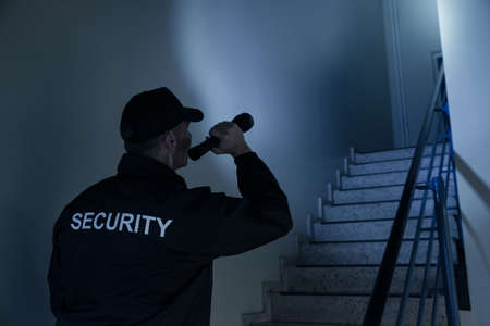 security uniform: Rear view of security guard searching on stairway with flashlight in office building