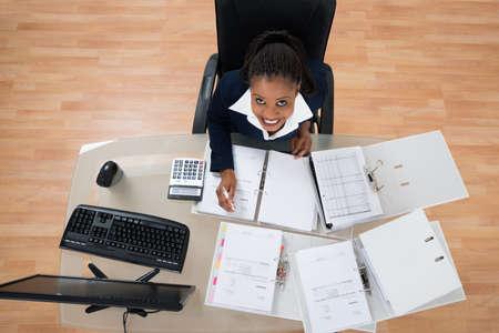High Angle View Of Businesswoman Calculating Bills Using Bills