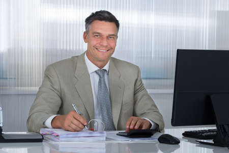 financial executive: Portrait of confident accountant using calculator while writing on documents at desk in office Stock Photo