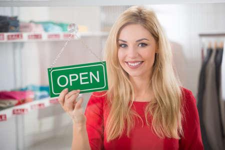 portada: Retrato de propietario femenino confía en celebración de la muestra abierta en la tienda de ropa Foto de archivo