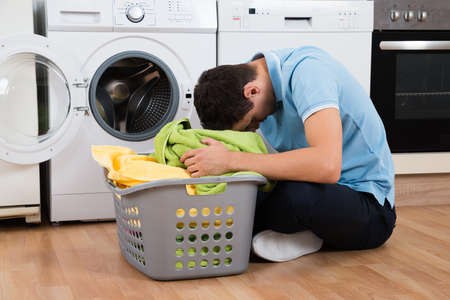 appliance: Exhausted young man with laundry basket sitting on floor by washing machine at home