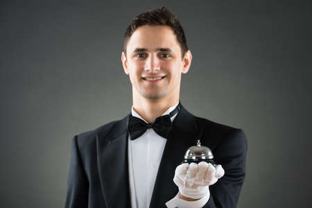 hospitality staff: Portrait of smiling young waiter holding service bell against gray background