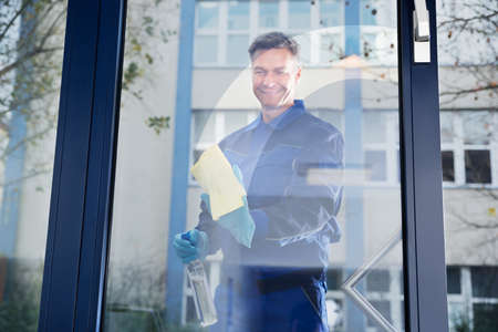house worker: Mature male janitor cleaning glass with rag