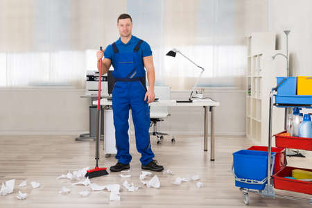 clean office: Full length of male janitor cleaning floor with broom in office