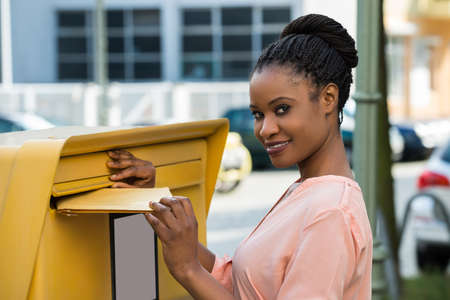 inserting: Young African Woman Inserting Letter In Mailbox