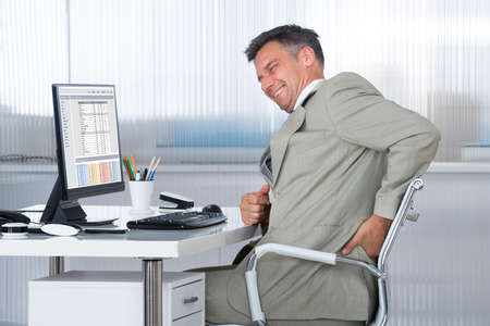 back ache: Side view of accountant suffering from back pain at desk in office