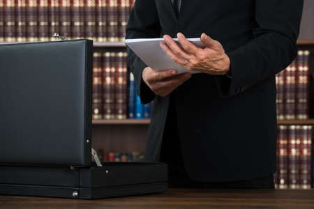 midsection: Midsection of male lawyer keeping documents in briefcase at table in office