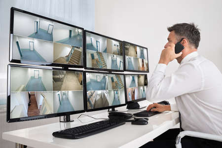 Seitenansicht des Sicherheitsnetzbetreiber mit Walkie-Talkie, w�hrend Sie auf CCTV footage