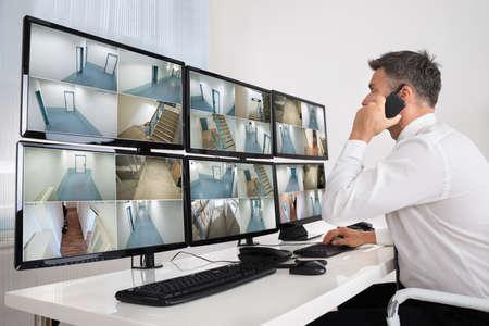 panel de control: Vista lateral del operador de sistema de seguridad con walkie-talkie mientras observa im�genes de CCTV