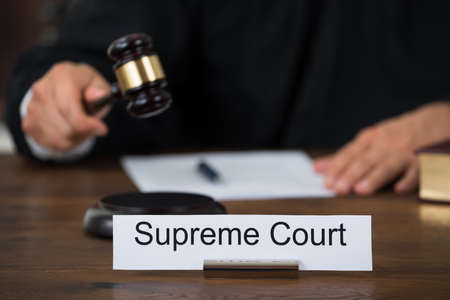 court: Supreme court nameplate with judge writing on paper at table in courtroom