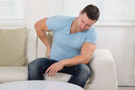 backpain: Mid adult man suffering from backpain while sitting on sofa at home