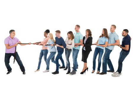 management team: Happy male leader pulling creative business team while playing tug of war against white background