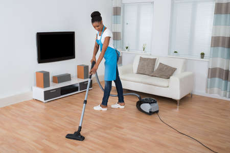black lady: Young African Woman Cleaning Hardwood Floor With Vacuum Cleaner