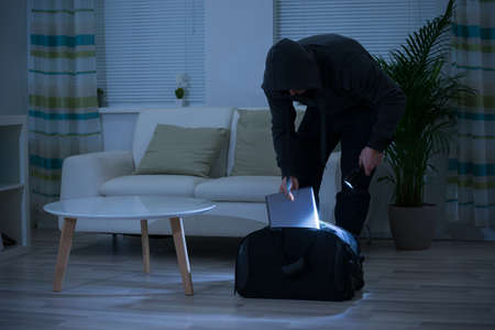 torchlight: Male burglar putting laptop into bag at home Stock Photo