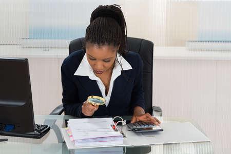 persone nere: Imprenditrice africana, guardando alla fattura tramite la lente d' Archivio Fotografico