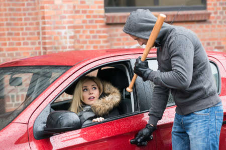 wrongdoing: Male robber holding baseball bat while looking at scared woman in car
