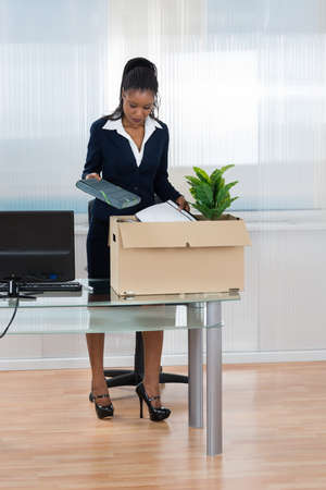 transferred: Young African Businesswoman Putting Her Belongings In Box At Office Desk