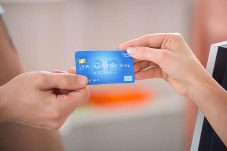 pagando: Imagen recortada de vendedor de tomar la tarjeta de crédito del cliente en almacén de ropa femenina Foto de archivo