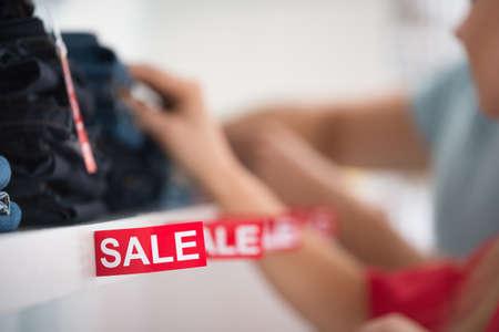 etiquetas de ropa: Primer de la muestra de la venta en la estantería con los pares en el fondo en la tienda de ropa Foto de archivo